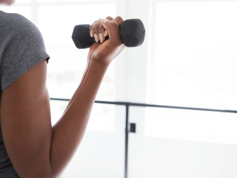 unwavering confidence. Girl holding a weight and doing a curl, showing strength and perseverance