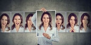 Pictures of a brunette holding a framed photo of herself with other photos behind her all with different facial expressions. This represents the importance of self-examination and being true to yourself in an honest way.