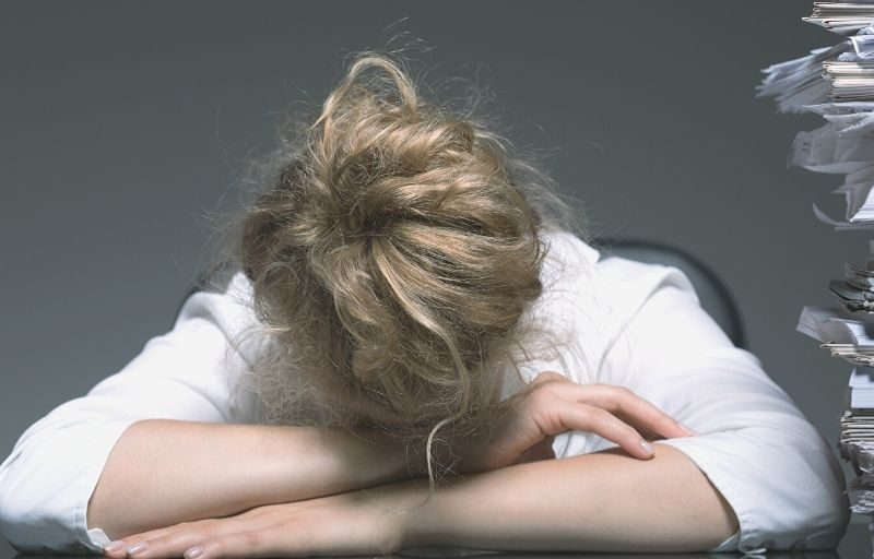 Woman exhausted with her head on the desk. A pile of papers haphazardly stacked next to her. Exhaustion can be avoided if you can balance the four areas of your life.