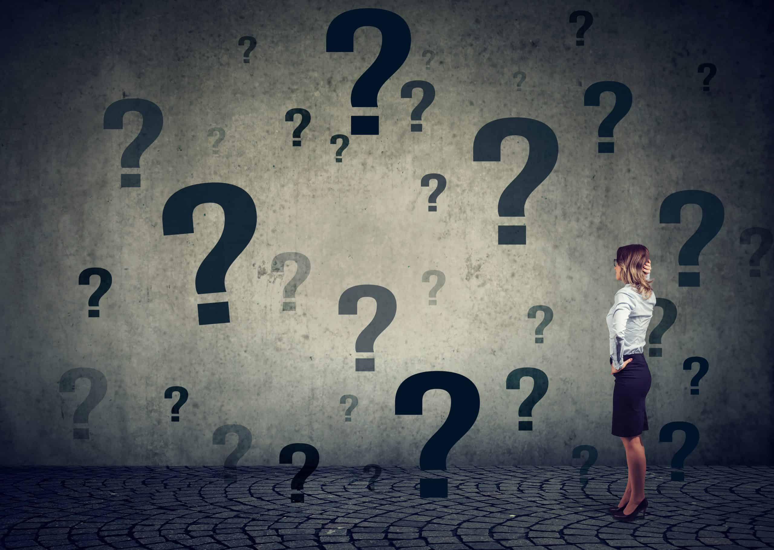 A woman surrounded by question marks. Self-Examination is the key to personal growth. Asking the right questions help you on your path to a clutter-free home.