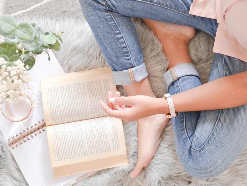 sitting cross-legged on the bed with an open book and journal, creating a meaningful morning ritual