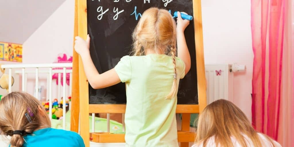 Child writing alphabet on chalkboard while siblings watch, a homeschooling benefit
